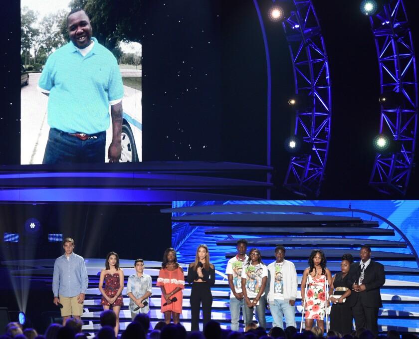 Jessica Alba, con familiares de víctimas de armas de fuego, ofrece un discurso mientras en una pantalla se proyecta una imagen de Alton Sterling durante los Premios Teen Choice en el Forum, el 31 de julio de 2016, en Inglewood, California. (Photo by Chris Pizzello/Invision/AP)