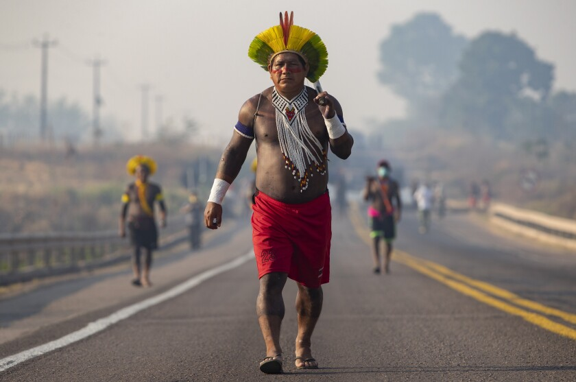 Kayapo Indigenous block a highway near Novo Progresso, Para state, Brazil, Monday, Aug. 17, 2020. Protesters blocked the highway BR-163 to pressure Brazilian President Jair Bolsonaro to better shield them from COVID-19, to extend damages payments for road construction near their land, and to consult them on a proposed railway to transport soybeans and corn. (AP Photo/Andre Penner)