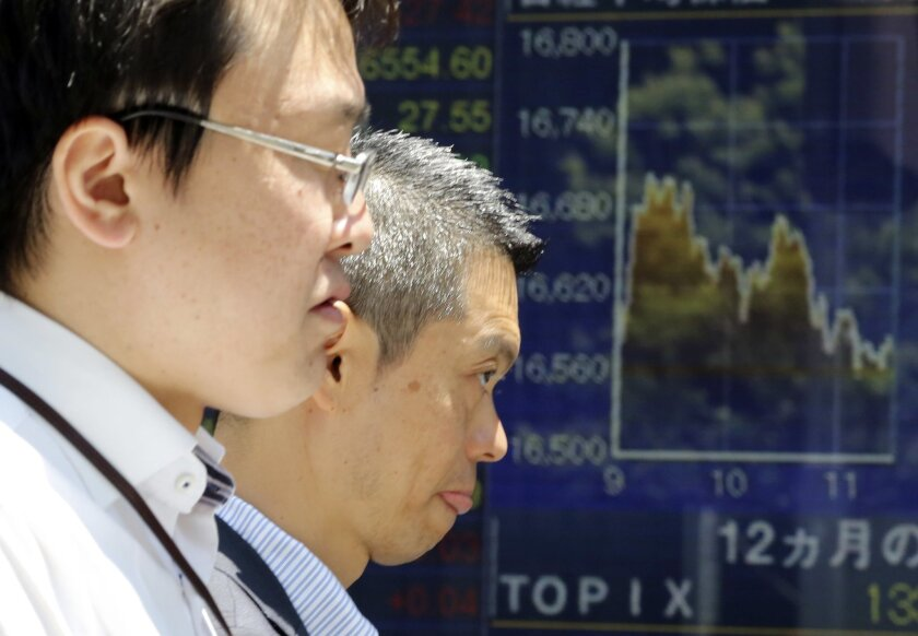 People walk by an electronic stock board of a securities firm in Tokyo, Friday, June 3, 2016. Asian shares were mixed Friday as investors awaited a U.S. jobs report later in the day and action from the U.S. Federal Reserve later in the month. (AP Photo/Koji Sasahara)