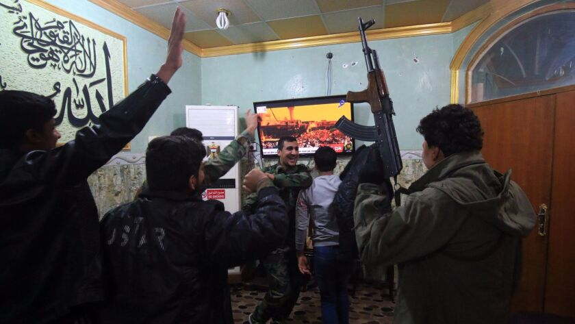 Members of the Hashd al Shaabi (Popular Mobilization Forces) watch the televised statement of Iraqi Prime Minister Haider Abadi in the southern city of Basra. Abadi declared victory in a three-year war by Iraqi forces to expel Islamic State.