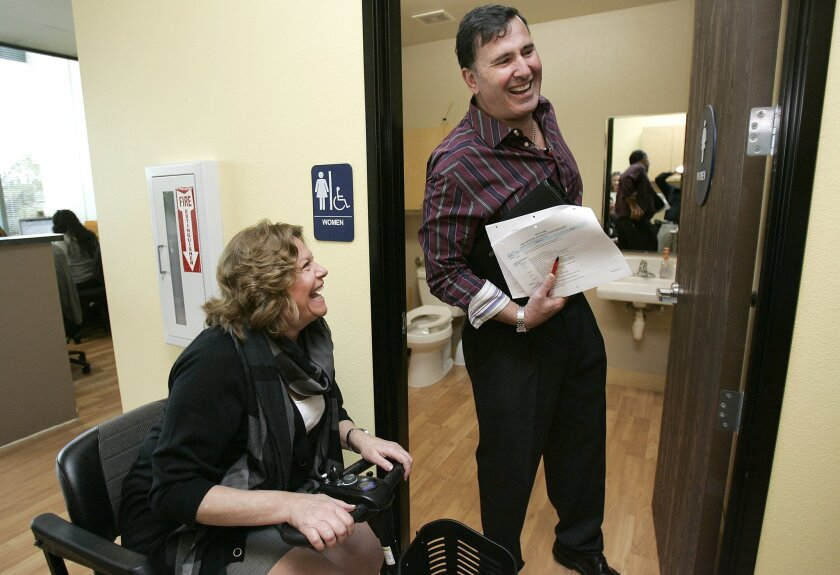 Steve Schraibman, a Certified Access Specialist, checks on building compliance with disabled access laws at the office of Bon Suisse in Poway. Failure to comply can lead to costly lawsuits.  Here, he inspects the women's bathroom, accompanied by company co-owner Elena Kassner.