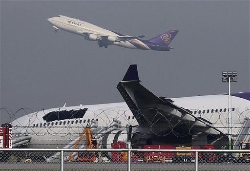 FILE - In this Monday, Sept. 9, 2013 file photo, a Thai Airways passenger plane takes off over a damaged Thai Airways Airbus A330-300 that skidded off the runway while landing at Suvarnabhumi International Airport in Bangkok, Thailand. The airline has ordered an inspection of its entire Airbus A330 fleet after this week's accident involving a model that Europe's air safety authority had warned years ago has a defective part in its landing gear. Airline officials said Friday, Sept. 13, they have