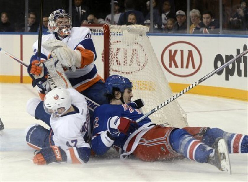 New York Rangers' Brian Boyle, right, and New York Islanders' Andrew MacDonald, center, crash into Islanders goalie Evgeni Nabokov during the second period of an NHL hockey game at Madison Square Garden in New York, Thursday, Feb. 14, 2013. (AP Photo/Henny Ray Abrams)