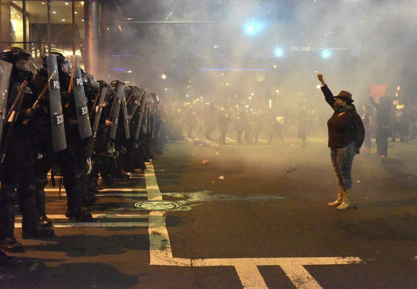 Manifestantes se encaran a policías antidisturbios con los brazos en alto durante unos disturbios en Charlotte en Carolina del Norte (Estados Unidos) el 21 de septiembre de 2016. El gobernador de Carolina del Norte, Pat McCrory, declaró el estado de emergencia en la ciudad de Charlotte, que vivió la segunda noche de disturbios tras la muerte de un afroamericano en un supuesto caso de violencia policial, protestas en las que otra persona resultó herida de bala. EFE/Caitlin Penna