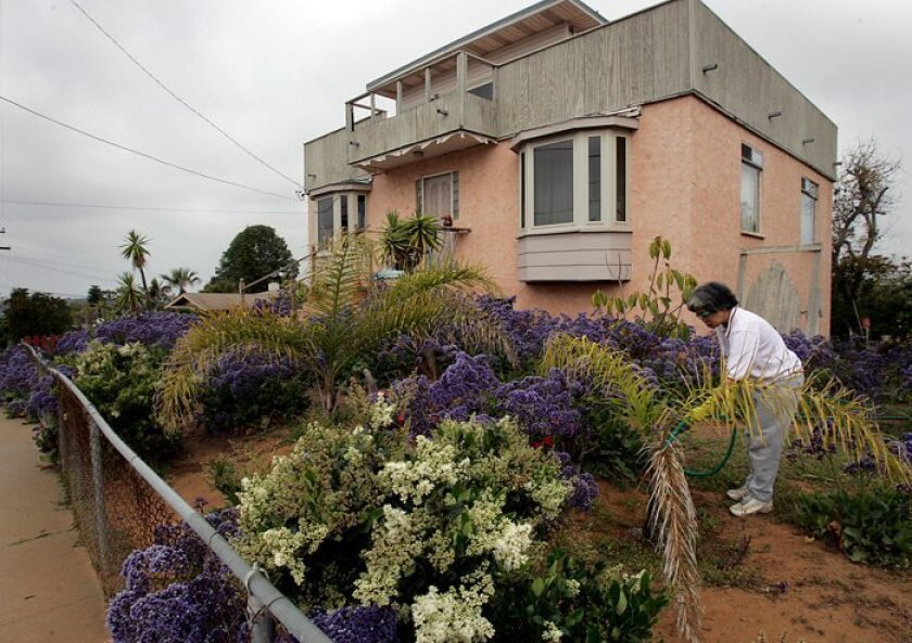 Elizabeth Bellazar waters plants in front of a home near the top of Fire Mountain, an Oceanside neighborhood known for its hills, views and beautiful homes.