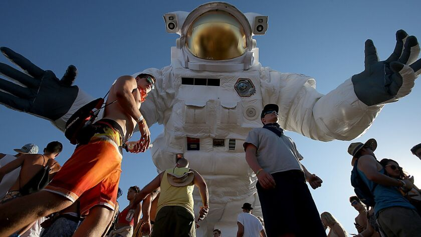 INDIO, CALIF. - APR. 11, 2014.Festival goers walk beneath a large inflatable astronaut on the first