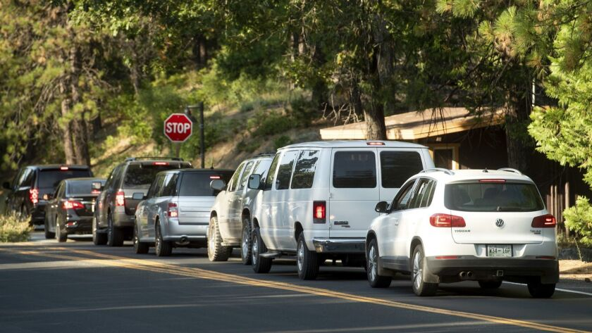 Vehicles leave Yosemite National Park, Calif., on Tuesday, July 24, 2018, as the Ferguson Fire burns