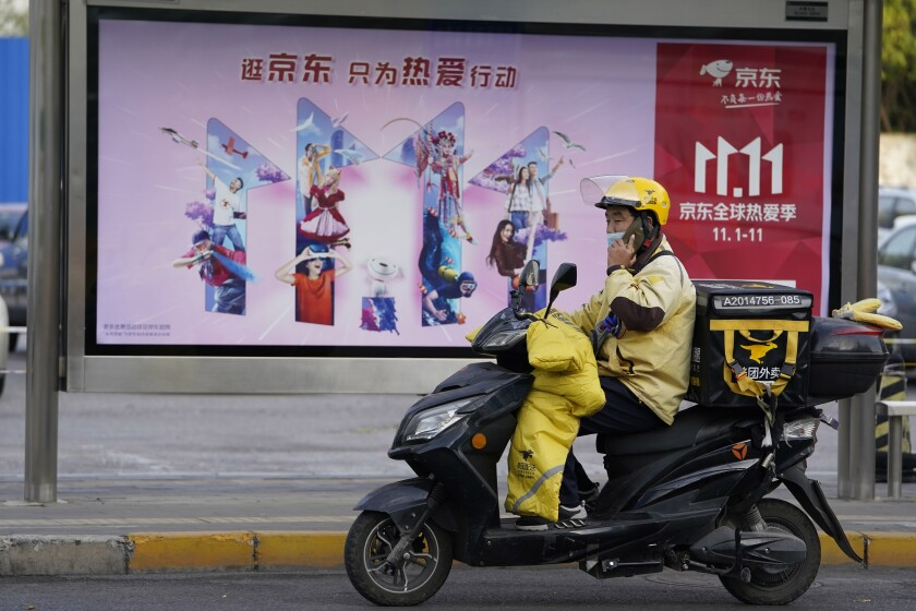 A delivery man passes by an ad for the Nov. 11 Sales Day in Beijing, China on Oct. 28, 2020. Chinese consumers are expected to spend tens of billions on everything from fresh food to luxury goods during this year's Singles' Day online shopping festival, as the country recovers from the coronavirus pandemic. (AP Photo/Ng Han Guan)