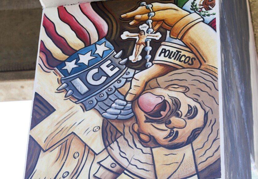 A detail of a mural at Chicano Park in San Diego shows a worker being oppressed by both sides of the border.