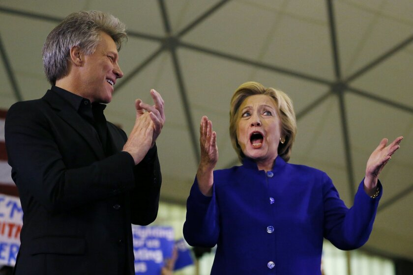 Democratic presidential candidate Hillary Clinton stands on stage with musician Bon Jovi during a campaign stop at the Newark campus of Rutgers University, Wednesday, June 1, 2016, in Newark, N.J. (AP Photo/Julio Cortez)