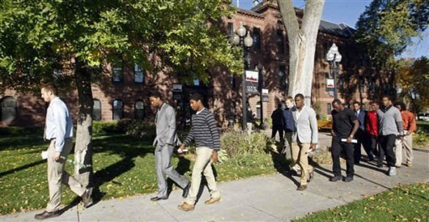 North Dakota State University football players, from left: Lucas Albers; Demitrius Gray; Charles Smith III; Josh Colville; Aireal Boyd; Antonio Rogers; Marcus Williams; Bryan Shepherd; Samuel Ojuri, and Brendin Pierre leave the Cass County Courthouse Tuesday, Oct. 2, 2012, in Fargo, N.D. The ten players pleaded guilty to misdemeanor election fraud and were sentenced to community service for faking signatures on proposed ballot measure petitions that they were hired to collect. (AP Photo/The Forum, David Samson)