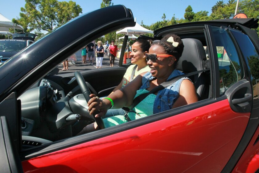 Keva Washington heads out for a test drive in a Smart Car as part of Electric Vehicle Day - San Diego. At left is Smart Car representative Ambar Bonilla.