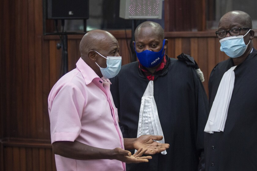 """Paul Rusesabagina, who inspired the film """"Hotel Rwanda"""" and is credited with saving more than 1,000 people by sheltering them at the hotel he managed during the genocide, speaks to lawyers as he attends a court hearing in Kigali, Rwanda, Friday, Feb. 26, 2021. The judge on Friday rejected Rusesabagina's argument in his terrorism trial that a court there cannot try him because he is no longer a citizen. (AP Photo/Muhizi Olivier)"""