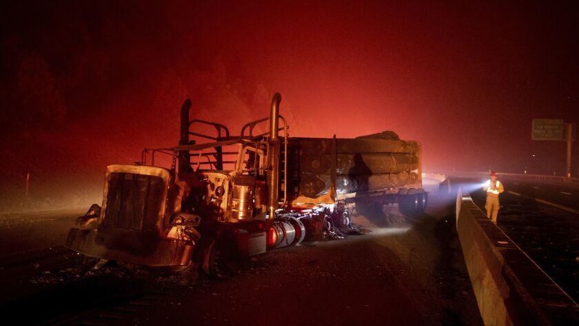 A scorched logging truck rests on the 5 Freeway as the Delta fire burns in the Shasta-Trinity National Forest.
