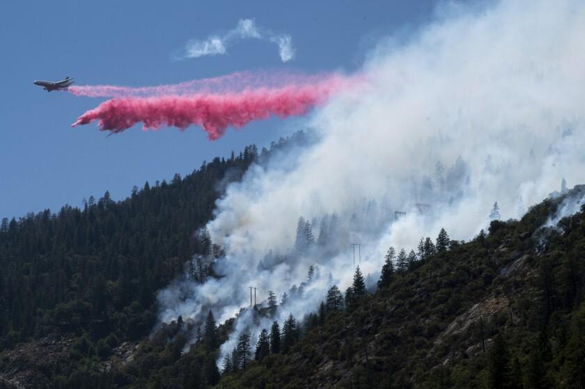 An air tanker drops pink fire retardant as white smoke rises above treetops.