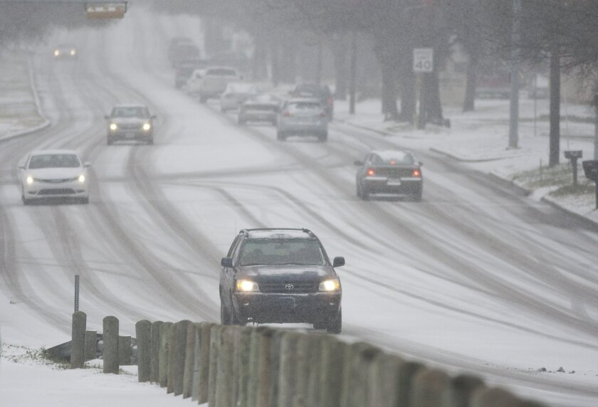 Traffic travels slowly along Davis Boulevard as snow falls, Friday, Feb. 27, 2015, in Arlington, Texas. Icy weather early in the week melted away by Wednesday afternoon, but Friday morning gave way to more snow and slippery roads in North Texas. (AP Photo/The Fort Worth Star-Telegram, Juan Guajardo) MAGS OUT; (FORT WORTH WEEKLY, 360 WEST); INTERNET OUT