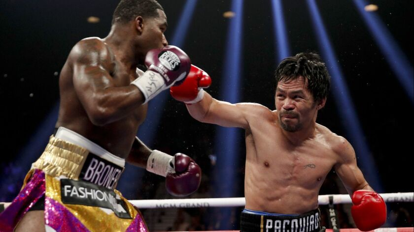 Manny Pacquiao, right, throws a right to Adrien Broner in the WBA welterweight title boxing match on Saturday in Las Vegas.