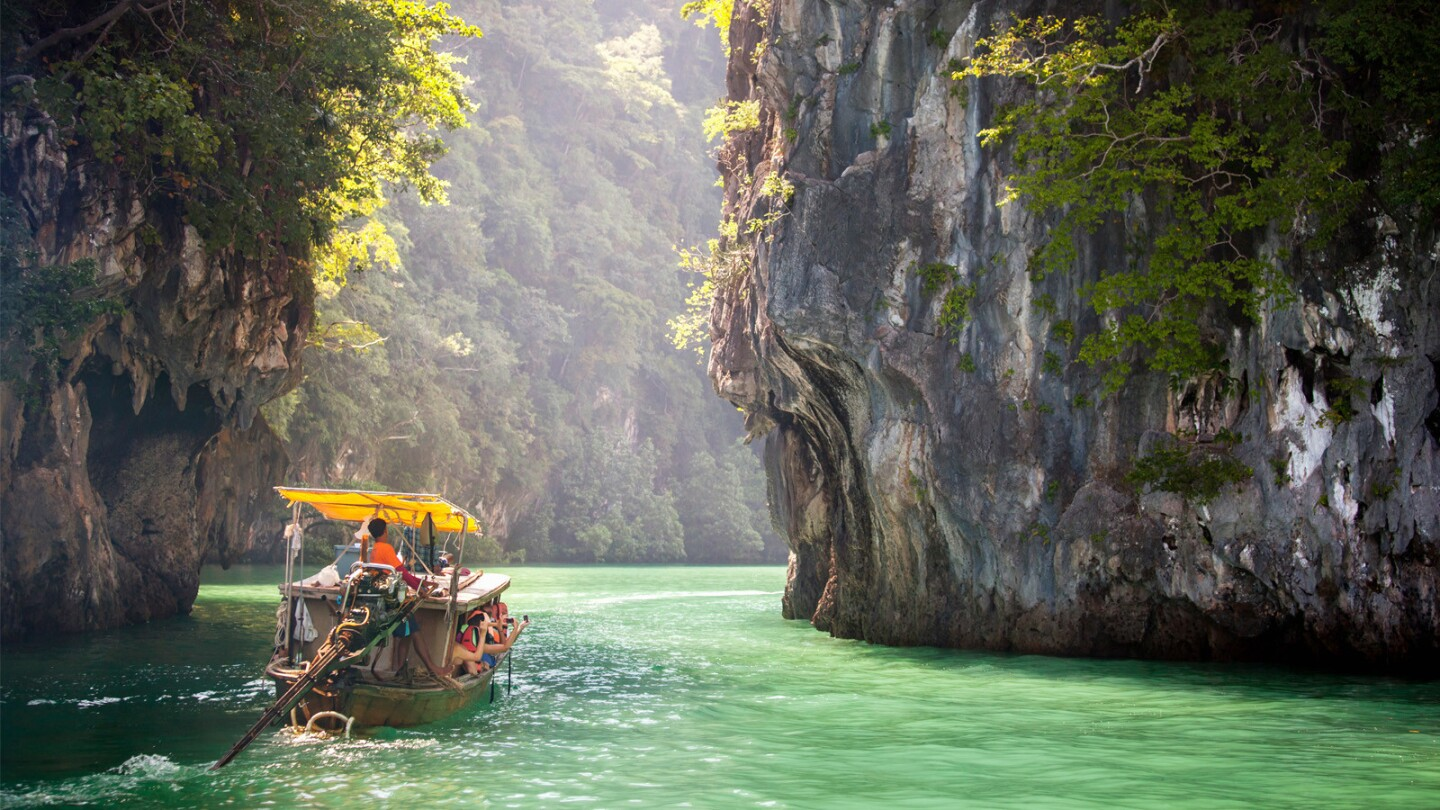 A long-tail boat plies the Andaman Sea off Krabi Province in Thailand.