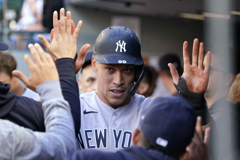 New York Yankees' Aaron Judge is congratulated after scoring against the Seattle Mariners during the first inning of a baseball game Wednesday, July 7, 2021, in Seattle. (AP Photo/Elaine Thompson)