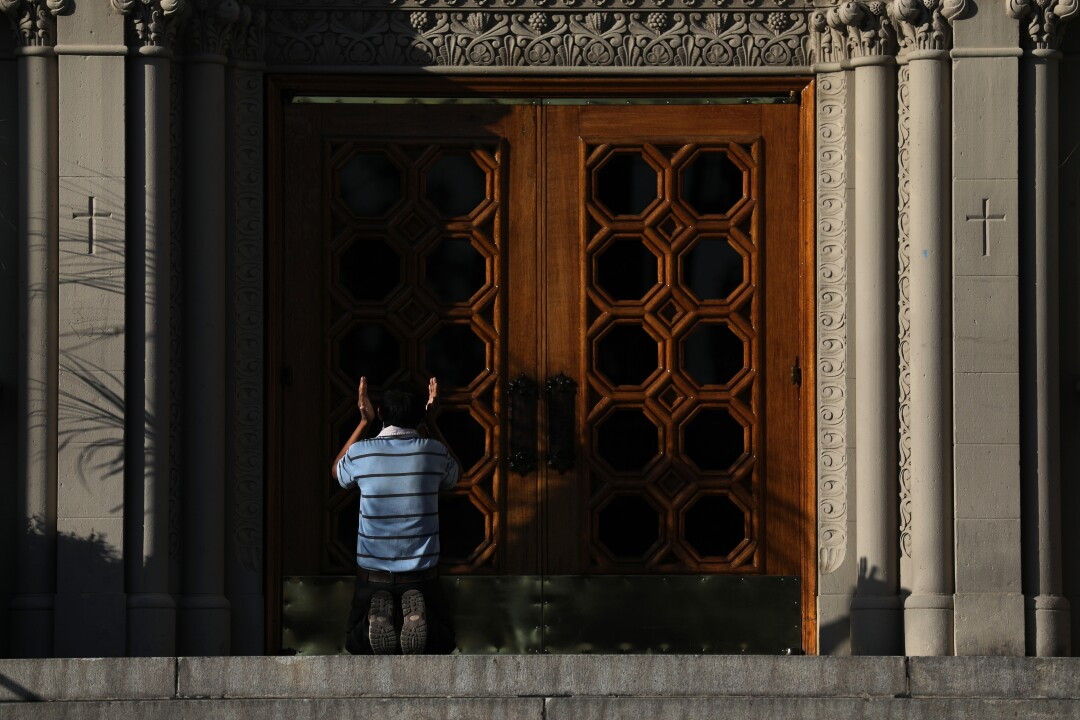 Man prays in front of the closed doors of the Immaculate Conception Catholic Church in downtown Los Angeles