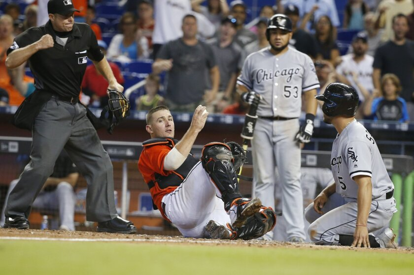 Miami Marlins catcher Jeff Mathis, second from left, holds on to the ball as home plate umpire Tripp Gibson, left, signals the out after Mathis tagged out Chicago White Sox pinch-runner Carlos Sanchez (5) at the plate to end the baseball game, Sunday, Aug. 14, 2016, in Miami. Sanchez tried to score