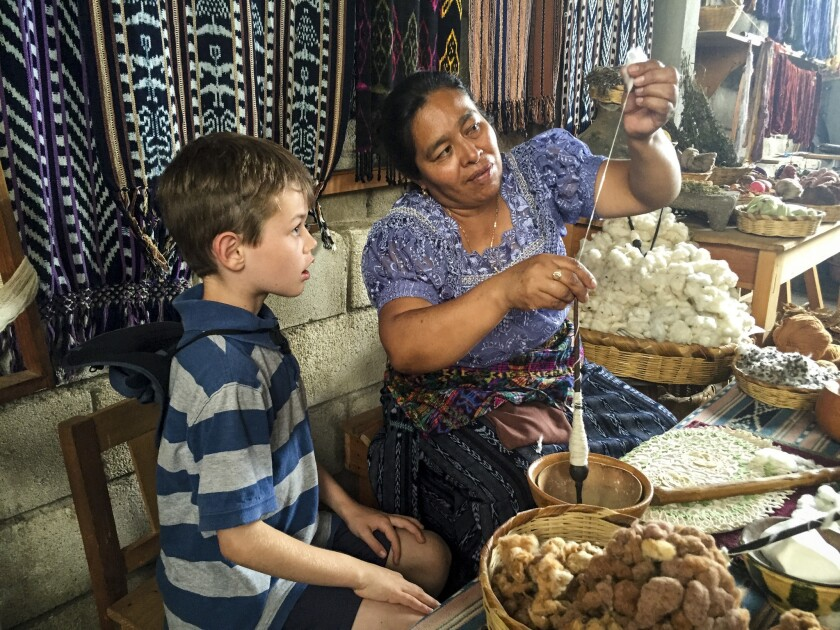 Liam learns to spin cotton during a weekend outing at a women's weaving cooperative in San Juan.