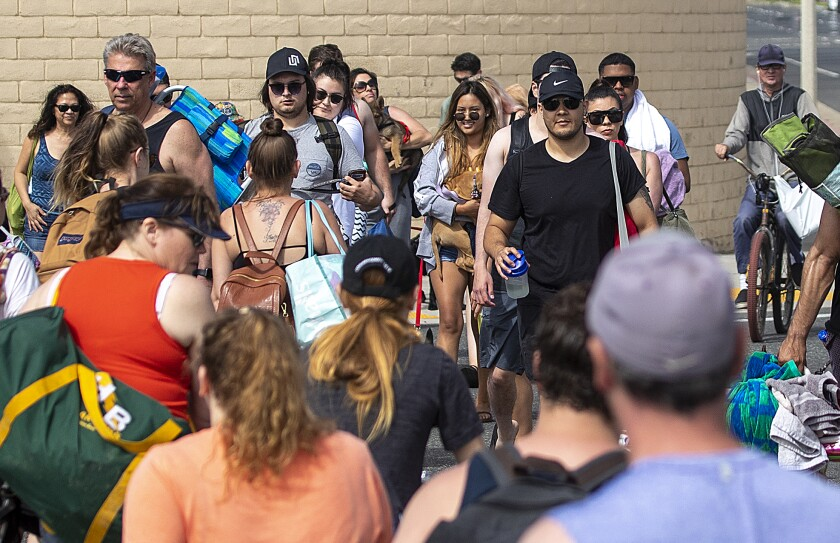 In late April in Huntington Beach, a crowd heads to the beach without social distancing or masks.