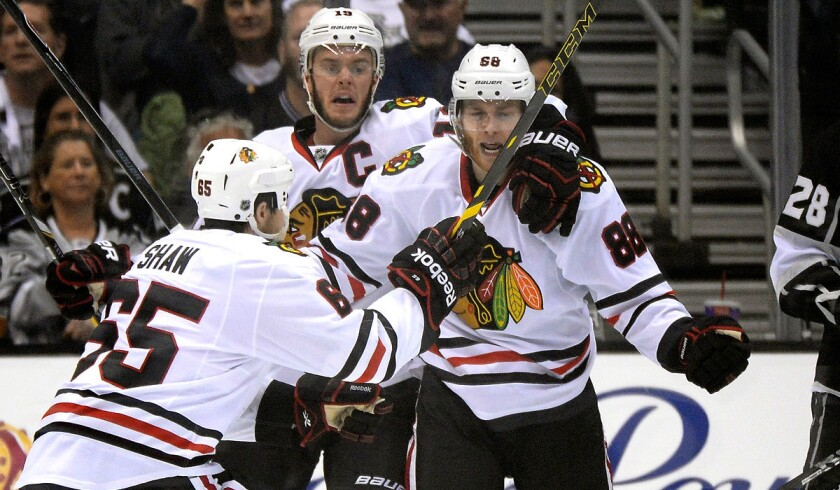 Blackhawks winger Patrick Kane (88) celebrates his goal in the second period with teammates Andrew Shaw (65) and Jonathan Toews (19) in Game 6 on Friday night at Staples Center.