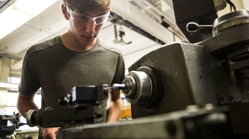 UCLA student Ben Gerber custom fabricates a part for the UCLA Formula SAE team car on a lathe in a m