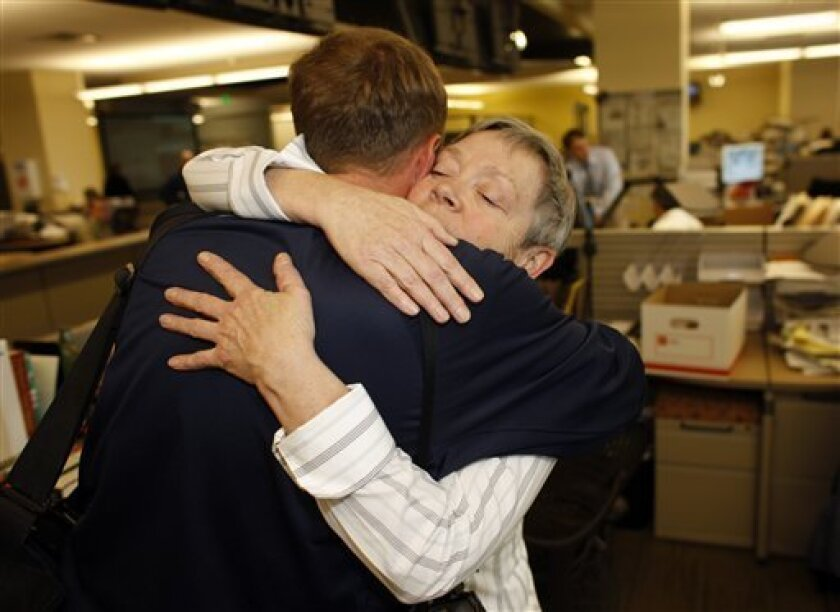 Jane Hoback, back, business editor of the Rocky Mountain News, hugs freelance photographer Marc Piscotty after the announcement that the paper will close in Denver on Thursday, Feb. 26, 2009. E.W. Scripps Co., owners of the News, which is Colorado's oldest newspaper dating back to 1859, announced o