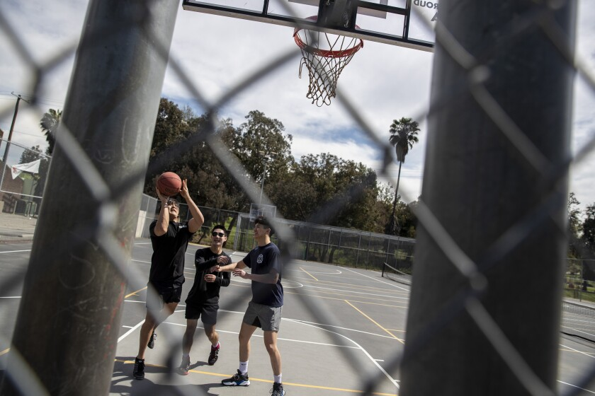 Timothy Chu, left, Michael Hashimoto and Kevin Liu on a basketball court at Hazard Park in L.A.