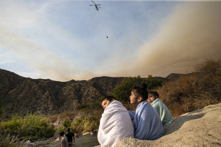 The Ranch2 fire burns nearby as three young children dry off  after swimming along the San Gabriel River