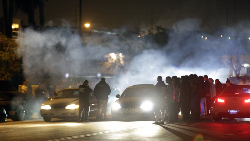 Two cars prepare to race on a smoke-shrouded street at night as spectators stand nearby
