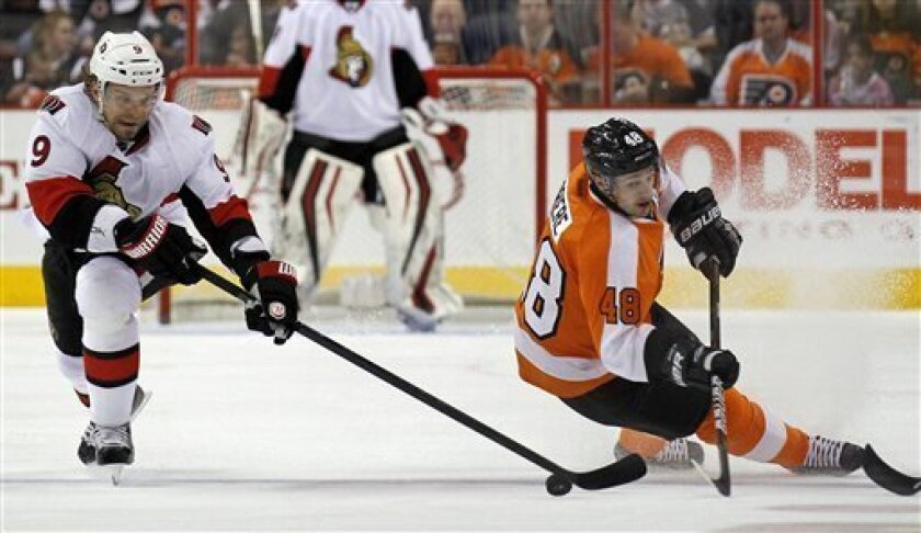 Ottawa Senators left wing Milan Michalek, left, from the Czech Republic, and Philadelphia Flyers center Danny Briere (48) go for the puck in the first period of an NHL hockey game Saturday, March 31, 2012 in Philadelphia. (AP Photo/Alex Brandon)