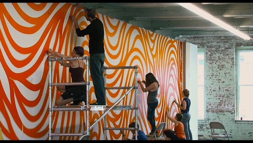 Installers use painted to produce a swirling orange pattern on a museum wall