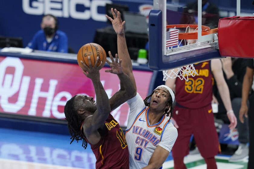 Cleveland Cavaliers forward Taurean Prince (12) shoots in front of Oklahoma City Thunder center Moses Brown (9) during the second half of an NBA basketball game Thursday, April 8, 2021, in Oklahoma City. (AP Photo/Sue Ogrocki)