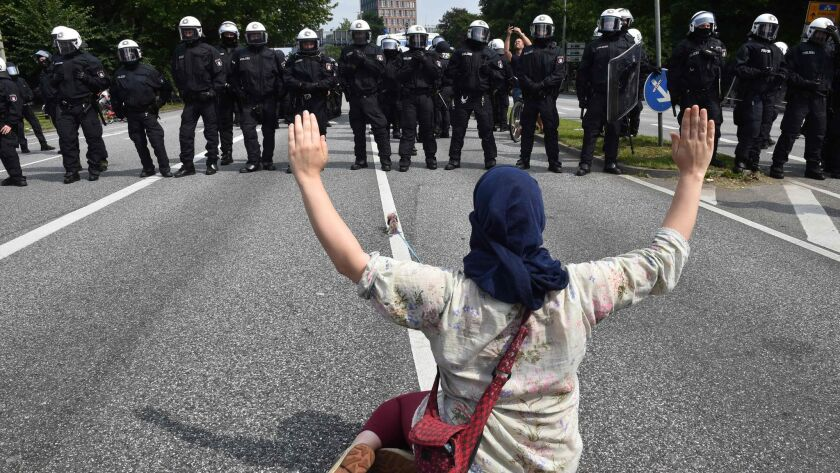 A demonstrator faces police officers during a July 7 protest in Hamburg Germany.