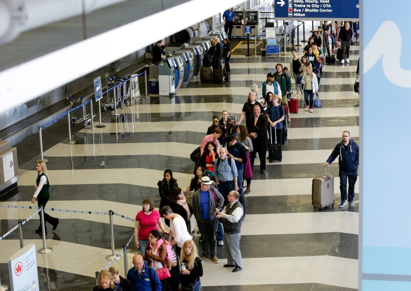 File-This May 16, 2016, file photo shows a long line of travelers waiting for the TSA security check point at O'Hare International airport, in Chicago. As airport security lines get longer, the finger-pointing over blame is growing too. The nation's leading airlines, already feuding with the Transportation Security Administration, are now taking on Congress. (AP Photo/Teresa Crawford)