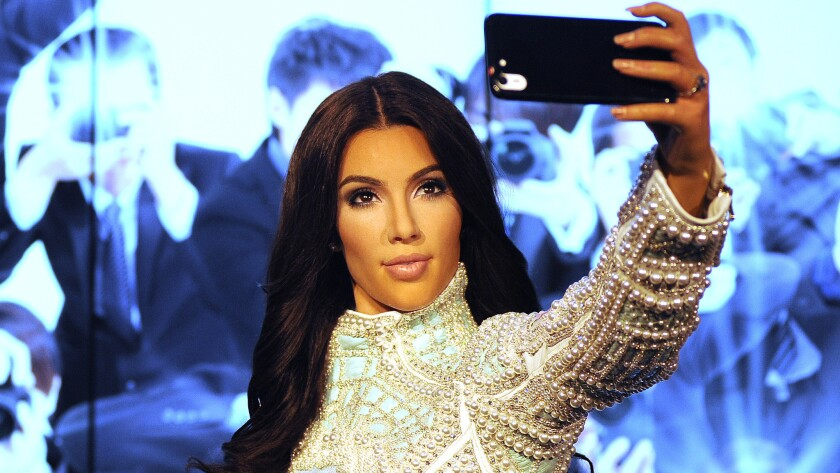 """""""Kim Kardashian"""" -- actually, a wax version of the reality star -- stands ready to snap a selfie at Madame Tussauds in London."""