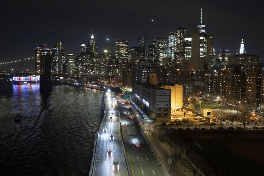 Cars head along FDR Drive next to the Manhattan skyline Thursday, March 26, 2020, during the coronavirus outbreak in New York. The New York City immortalized in song and scene has been swapped out for the last few months with the virus version. In all the unknowing of what the future holds, there's faith in that other quintessential facet of New York City: that the city will adapt. (AP Photo/Mark Lennihan)