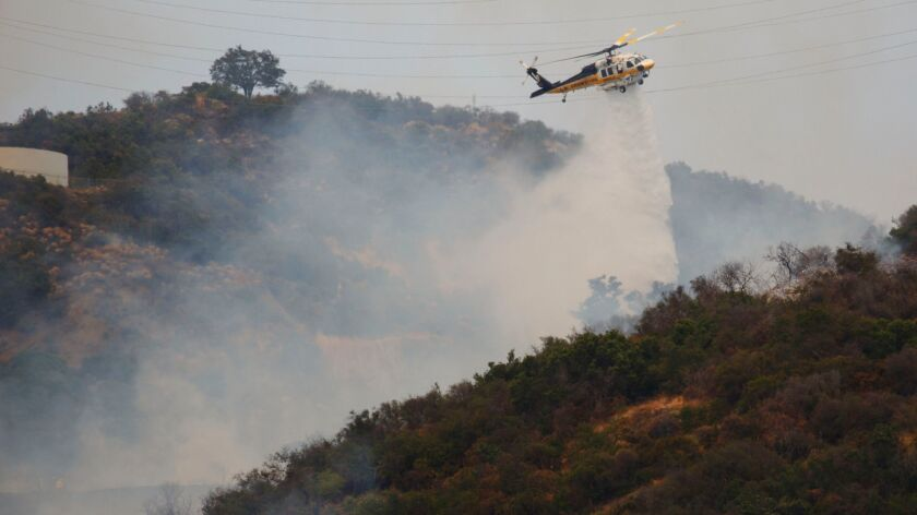 An LA County firefighting helicopter makes a drop as firefighters battle a brush fire in the Mandevi
