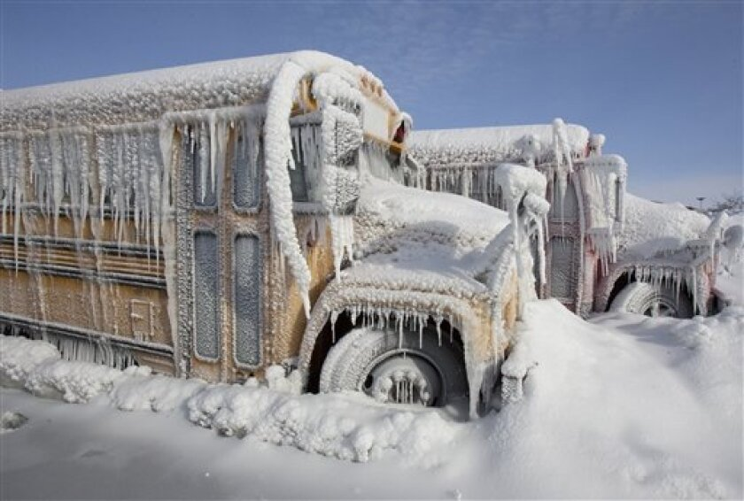 Buses are encrusted in ice and snow at the back lot of a bowling alley in the Omaha, Neb., suburb of Elkhorn, where a fire was being put out, Thursday, Jan. 7, 2010. A winter storm with bitter cold temperatures and blowing winds is traveling through the region. (AP Photo/Nati Harnik)