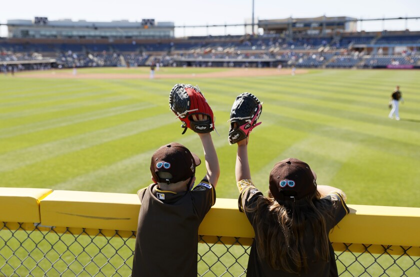 Two young fans watch the Padres and Cubs play Monday at Peoria Stadium.