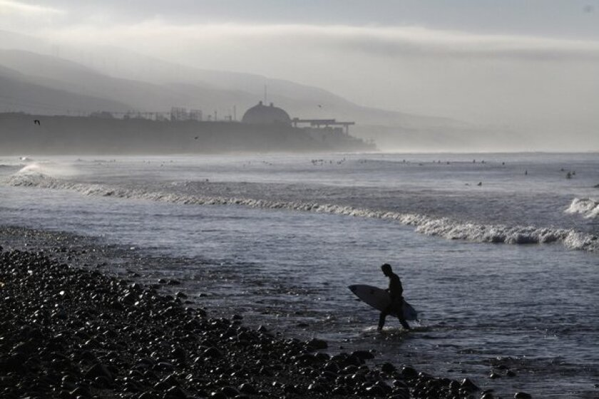 An early morning surfer, with the San Onofre nuclear power plant in the background, catches a few waves as fog clears at Lower Trestles in San Clemente.
