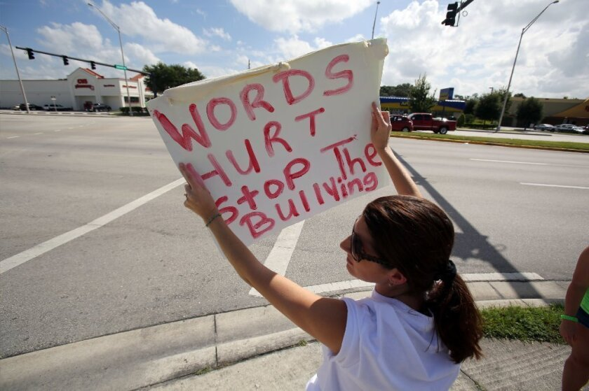 Kids and teens who are taunted by bullies are more likely to consider and to attempt suicide, a new study has found. Above, a woman holds a sign against bullying in Lakeland, Fla., last year.