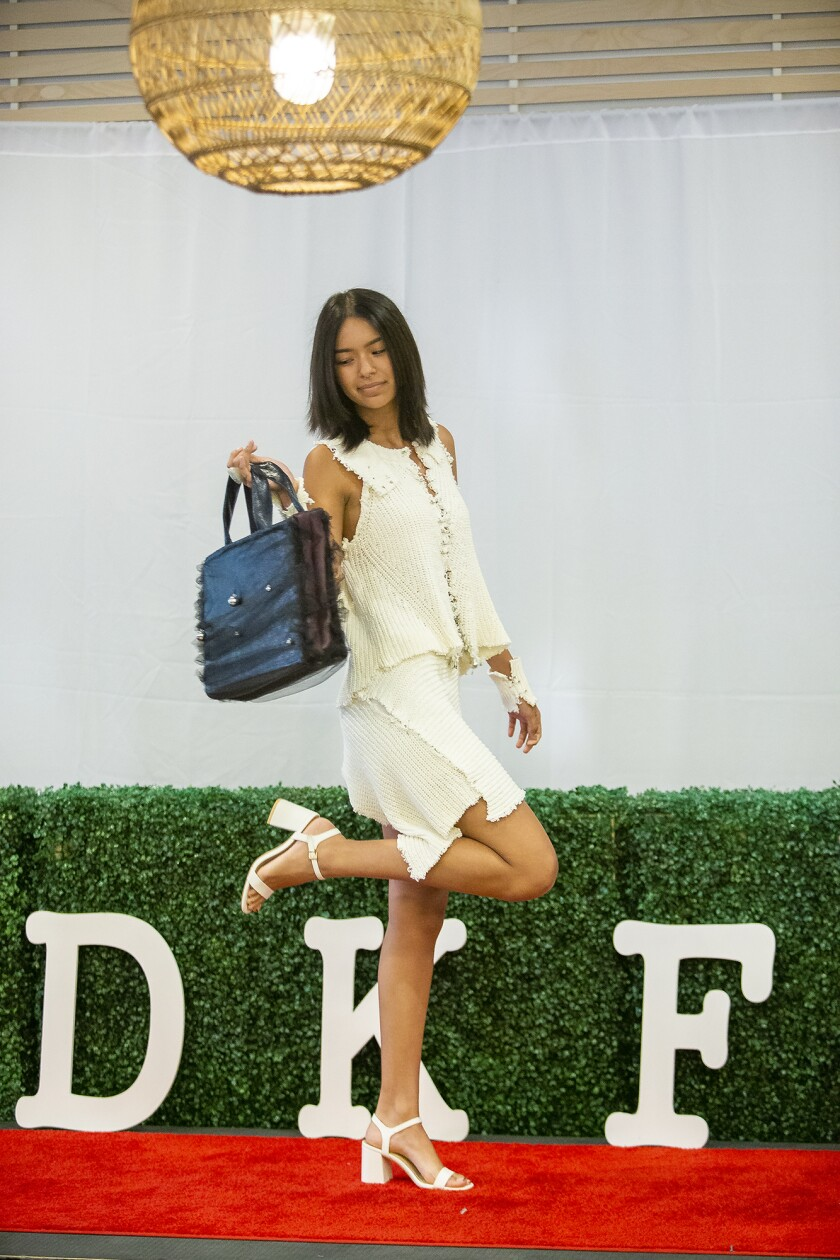 """Cris Tinaeily shows off a handbag designed by Team Opia during a """"Young people in fashion"""" Thursday fashion show at South Coast Plaza."""