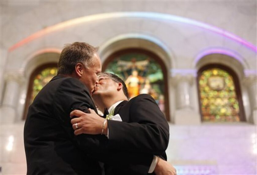 Jeff Isaacson, left, and Al Giraud, right, kiss for the first time as a married couple during the Minneapolis Freedom to Marry Celebration and Weddings at the Minneapolis City Hall, Thursday, Aug. 1, 2013. The two were the first men to be married legally in Minnesota. (AP Photo/Stacy Bengs)
