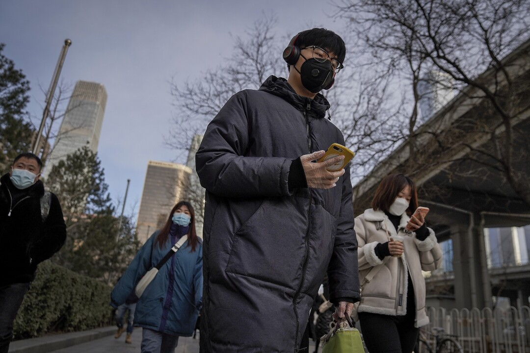A man wearing a mask heads to work in Beijing.