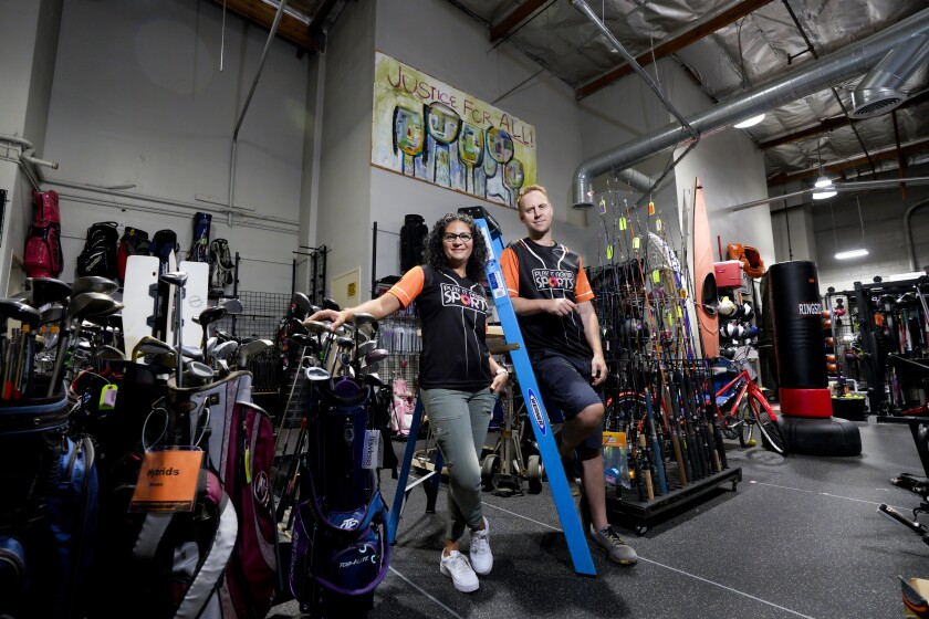 Play It Again Sports store owners Mary and Dan Buxton stand next to a large mural at their sporting goods store.