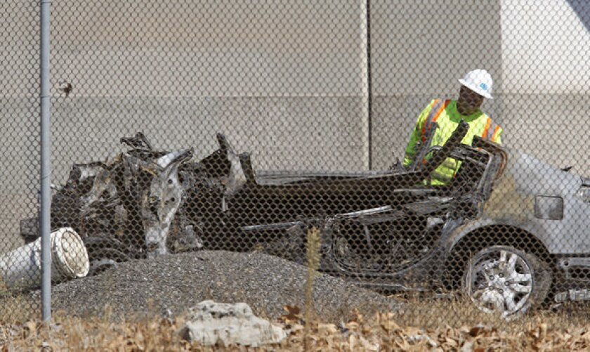 A workman examines the burned-out Nissan wreckage of a crash that killed five young people. The driver had more than twice the legal limit of alcohol in his system at the time, a coroner's report determined.
